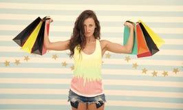Silni shopaholic dziewczyna chwyta torba na zakupy Pi?kny shopaholic dziewczyna trzyma kolorowe papierowe torby w silnych r?kach  obraz stock
