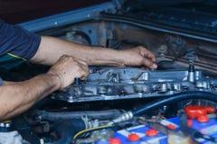 Silnik naprawa, mechanik pracuje w samochodzie pod kapiszonem Zdjęcia Royalty Free