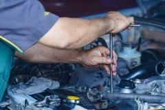 Silnik naprawa, mechanik pracuje w samochodzie pod kapiszonem Zdjęcie Royalty Free