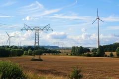 Silniki wiatrowi i elektryczność pilony w wiejscy krajobrazowi agains Zdjęcie Stock