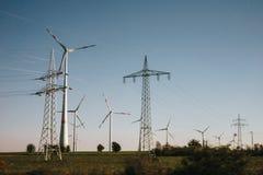 Silniki wiatrowi i linie energetyczne na polu zdjęcia stock
