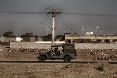 Silniki wiatrowi, kamieni domy, linie energetyczne, ludzie w wojsko dżipie zdjęcia royalty free