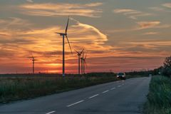 Silniki wiatrowi wytwarza elektryczność obok drogi przy zmierzchem, w obraz royalty free