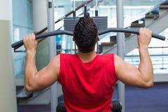 Silny bodybuilder używa ciężar maszynę dla ręk fotografia stock