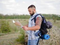 Silny brodaty wycieczkuje przewdonik patrzeje mapę na naturalnym tle pomocy tła plecaka kompasu pojęcia wyposażenie najpierw targ Zdjęcia Royalty Free