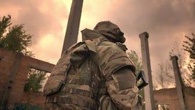 Silny caucasian oficer jest ubranym kamuflaż przez zaniechanego budynku samotnie my odprowadzenie, mienie broń, patrzeje naprzód zdjęcie wideo