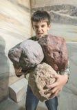 Silny dziecko trzyma ciężkich kamienie Obrazy Stock