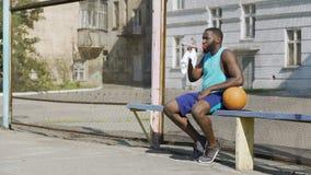 Silny gracza koszykówki obsiadanie na ławce i pić wodzie mineralnej, sport zdjęcie wideo