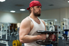Silny mężczyzna, bodybuilder ćwiczy z dumbbells w gym Fotografia Stock