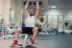 Silny mężczyzna, bodybuilder ćwiczy z dumbbells w gym Zdjęcia Royalty Free