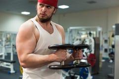 Silny mężczyzna, bodybuilder ćwiczy z dumbbells w gym Zdjęcie Royalty Free