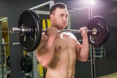 Silny mężczyzna - bodybuilder z dumbbells w gym, ćwiczy z barbell Obraz Stock