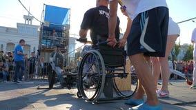 Silny mężczyzna obezwładniający na koła krzesła ciągnieniach depeszuje przy sporta wydarzeniem z trenerem w świetle słonecznym zbiory wideo