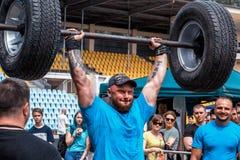 Silny mężczyzna podnosi ciężkiego barbell weightlifting Zdjęcia Stock
