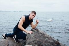 Silny mężczyzna postępuje joga na skałach wyrzucać na brzeg w ranku przeciw morzu Obrazy Royalty Free