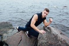 Silny mężczyzna postępuje joga na skałach wyrzucać na brzeg w ranku przeciw morzu Fotografia Stock
