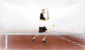 Silny mężczyzna trzyma tenisowego kant i piłkę podczas gdy trenujący Obraz Royalty Free