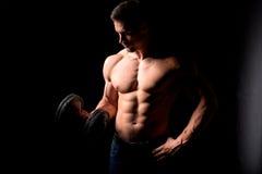 Silny mężczyzna z mięśniowym ciałem pracującym out Ciężaru ćwiczenie z dumbbell na czarnym tle Zdjęcia Stock