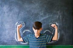 Silny Męski dziecko Pokazuje mięśnie W sala lekcyjnej Przy lekcją Zdjęcie Royalty Free