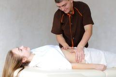Silny męski masażysta z delikatnymi ręka ruchami ugniata brzucha c Obraz Royalty Free