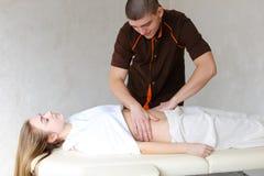 Silny męski masażysta z delikatnymi ręka ruchami ugniata brzucha c Zdjęcia Royalty Free