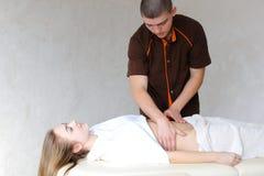 Silny męski masażysta z delikatnymi ręka ruchami ugniata brzucha c Obraz Stock