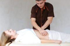Silny męski masażysta z delikatnymi ręka ruchami ugniata brzucha c Fotografia Royalty Free