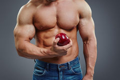 Silny mięśnia mężczyzna trzyma Czerwonego Apple Fotografia Stock