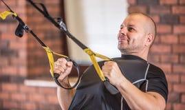 Silny mięśniowy mężczyzna ćwiczy z trx udostępnieniami w gym lub wor obraz royalty free