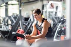 Silny Mięśniowy mężczyzna odpoczywa Wśród maszyn w Gym fotografia royalty free