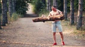 Silny mięśniowy mężczyzna podnosi a logował się lasową drogę zbiory