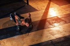 Silny mięśniowy mężczyzna podnosi w gym robić pcha Obrazy Stock