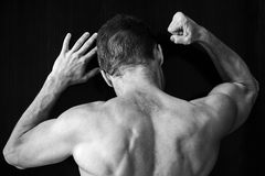 Silny mięśniowy młody Kaukaski mężczyzna puka na czerni ścianie z cześć Zdjęcie Royalty Free