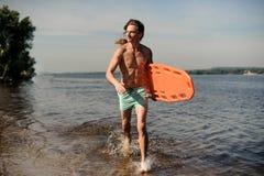 Silny seksowny plażowy ratownika bieg wzdłuż brzeg rzeki z li Fotografia Stock