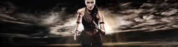 Silny sportowy kobieta szybkobiegacz, biega na ciemnym tle jest ubranym w sportswear Sprawności fizycznej i sporta motywacja bieg obrazy stock