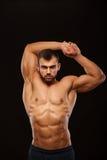 Silny Sportowy mężczyzna - sprawność fizyczna model pokazuje jego półpostać z sześć paczek abs i trzyma jego ręki up Odizolowywaj Zdjęcia Stock