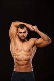 Silny Sportowy mężczyzna - sprawność fizyczna model pokazuje jego półpostać z sześć paczek abs i trzyma jego ręki up Odizolowywaj Zdjęcie Royalty Free