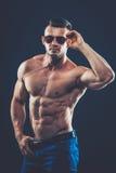 silny sportowy mężczyzna w okularach przeciwsłonecznych na czarnym tle Zdjęcie Stock