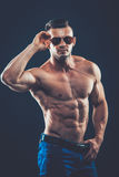 silny sportowy mężczyzna w okularach przeciwsłonecznych na czarnym tle Zdjęcie Royalty Free