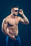 Silny sportowy mężczyzna w okularach przeciwsłonecznych na czerni Zdjęcie Royalty Free