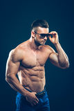 Silny sportowy mężczyzna w okularach przeciwsłonecznych na czerni Obraz Royalty Free
