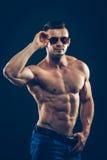 Silny sportowy mężczyzna w okularach przeciwsłonecznych na czerni Obrazy Royalty Free