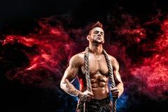 Silny sportowy mężczyzna z nagim ciałem w wojskowych spodniach i arkana na szyi czernimy Fotografia Royalty Free