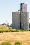 Silo de grano al lado de un campo cosechado Imágenes de archivo libres de regalías