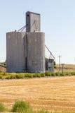 Silo de grano al lado de un campo cosechado Fotos de archivo libres de regalías