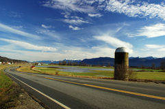 Silo de grano por el camino Fotografía de archivo libre de regalías