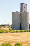 Silo di grano accanto ad un campo raccolto Immagini Stock Libere da Diritti
