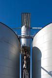 Silo Drob Tube. Shot taken of two silos and their drop tube inbetween.against blue sky Royalty Free Stock Photo