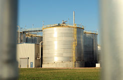 Silo of Ethanol Plant. Large silo of ethanol plant viewed through silver metal pipes Stock Images