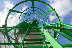 Silo Ladder. Vertical metal ladder green. Silo for storing road salt overlooking the snow season. Staircase to blue sky with clouds with safety rails and screens Royalty Free Stock Photos